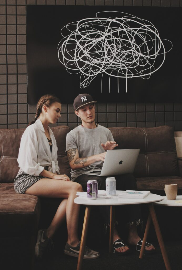 How Much do Sober Living Homes Cost, Two People Sitting on a Couch Looking at a Computer Screen, Foundations Wellness Center